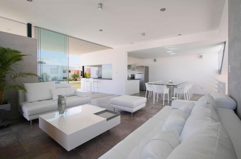 Sala com móveis brancos que aumentam a amplitude do espaço