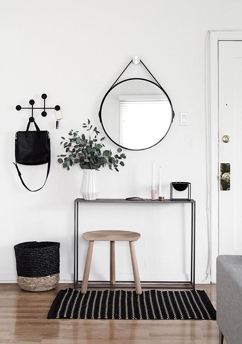 Aparador, espelho redondo e cabide para bolsa em entrada de casa